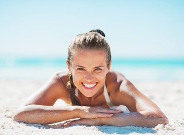 Portrait Of Smiling Young Woman In Swimsuit Laying On Sandy Beac