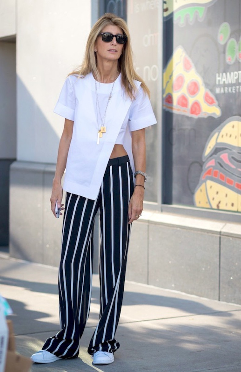 le-fashion-blog-street-style-sarah-rutson-nyfw-white-asymmetrical-top-striped-wide-leg-pants-sneakers-via-the-urban-spotter