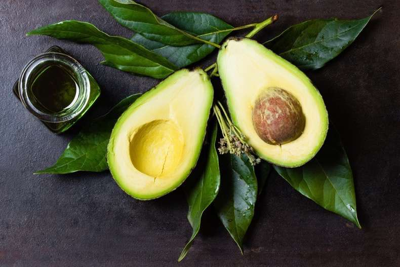 Avocado with leaves and jar of oil on black background top view